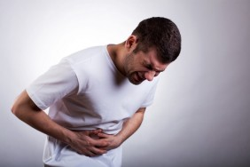 Young man with severe stomach ache holding his stomach